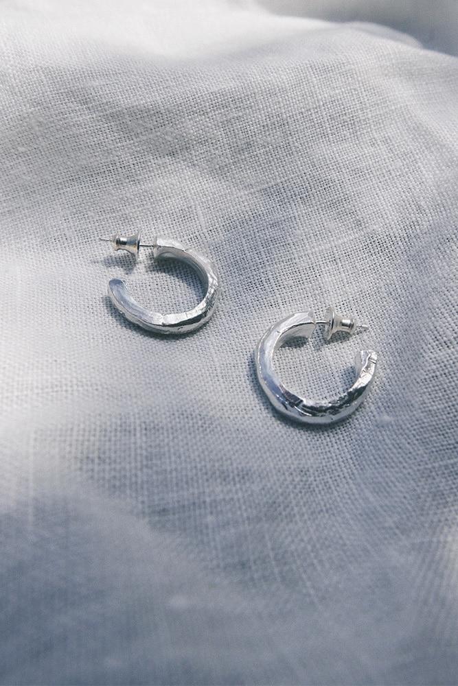 a pair of organic shape hoop earrings in silver